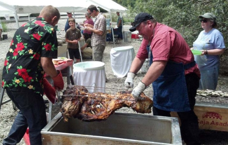 Mike Simila and Darrel Rogers wrestle the first wild pig out of the roasting box.